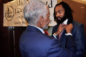 John C. Brittain passes the torch, giving his Guild pin to UDC NLG President, Naji Mujahid.