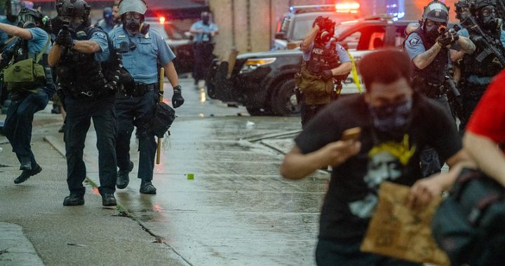 A group of police officers in blue shirts approach down a wet street with guns pointed toward protestors who duck their heads and run away from them. There are cop cars with lights flashing in the background.