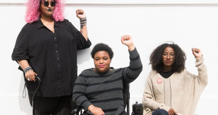 Torso level photo of three Black and disabled folx (a non-binary person holding a cane, a woman in a power wheelchair, and a woman on a folding chair) raising their fists on the sidewalk in front of a white wall. Credit: Disabled and Here