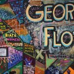 """A colorful wall memorial dedicated to George Floyd has different phrases written across it in different people's handwritings with phrases such as """"Black Women Matter"""" and """"8 minutes, 46 seconds"""""""