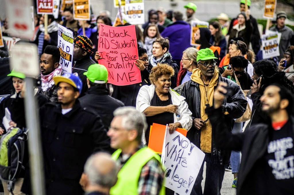 In a crowd of anti-racist activists holding signs in support of Ferguson and denouncing police brutality, there are 5 folks wearing neon green hats.  One of them, a black man with glasses, faces the camera. He is NLG Legal Observer Blair Anderson.